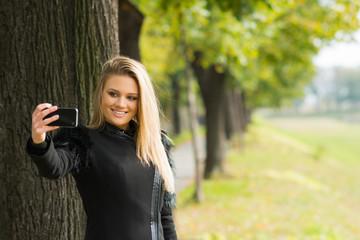 Fashionable teenage girl in black coat taking a selfie in park