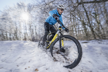 Mountain biker riding a bike in a snowy forest, Bavaria, Germany