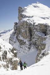Skier's climbing on snowcapped mountain