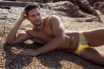 Sexy man lying on the beach