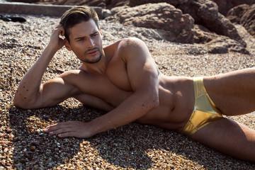 Sexy man lying on the beach