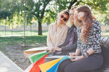 Three beautiful girls resting in the park after shopping