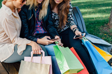 Girls hold shopping bags and using mobile phones