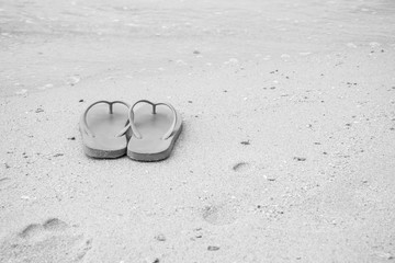 slippers and flower on the beach background - monochrome
