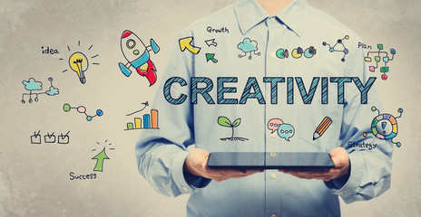 Creativity concept with young man holding a tablet