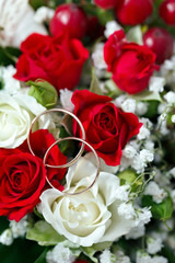 Golden wedding ring on the bride's bouquet. Bouquet of red and w