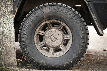Dirty car wheel stands on rural road