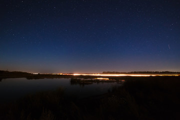 The stars in the night sky reflected in the river. The lights fr