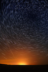 Star trail in the night sky against the backdrop of city lightin