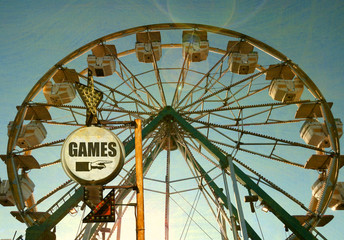aged and worn vintage photo of carnival games sign with ferris wheel