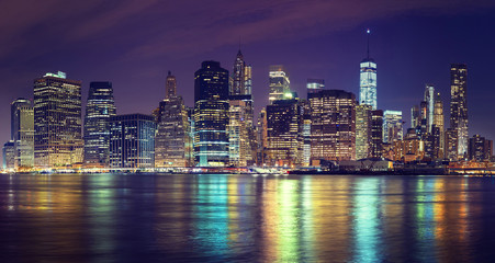 Vintage toned Manhattan skyline at night, NYC, USA.