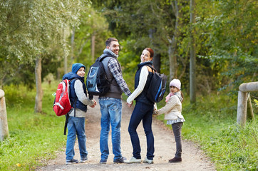 happy family with backpacks hiking walking