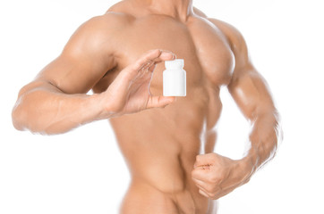 Bodybuilding and chemical additives: handsome strong bodybuilder holding a white jar of pills on white isolated background in studio