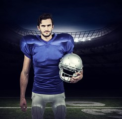 Composite image of american football player holding an helmet