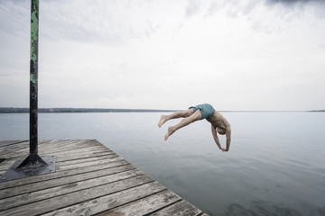 Mature man jumping into water on pier, Bavaria, Germany