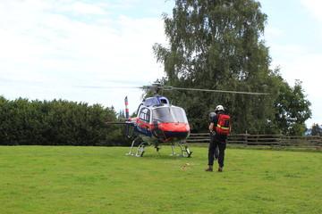 Hubschrauber wird bei der Landung am Landeplatz von einem Flughelfer eingewiesen