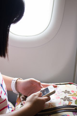 The girl using smart phone on the airplane