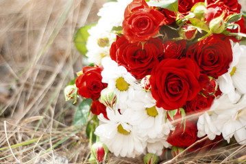 wedding bouquet of red roses on the grass