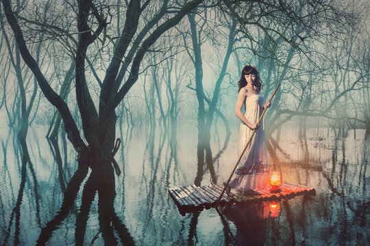 Woman on a raft with a lantern floating on a pond in a misty forest. Fairy tale woman in a long dress.