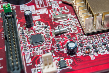red computer motherboard with electrical components