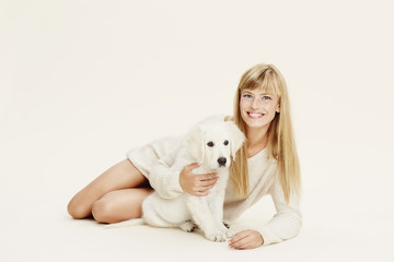 Blond woman and puppy lying in studio