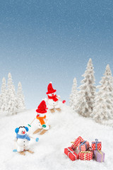 Happy snowmen skiing down the hill finding christmas gift in the snow.