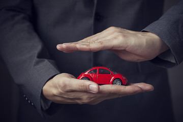 Businessman in suit with two hands in position to protect a car (focus on hand, blur out the suit). It indicates many aspects such as car insurance coverage, support, assurance, reliability.