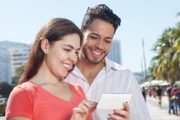 Paar in der Stadt schaut Fotos auf dem Handy an