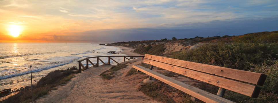 Bench along an outlook with a view at sunset of Crystal Cove Beach, Newport Beach and Laguna Beach line in Southern California