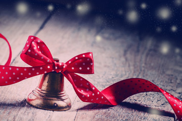 Jingle bells with a red ribbon with polka dots on old wooden bac