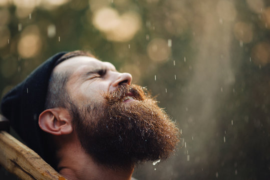 bearded brutal man in warm hat lumberjack with an ax in a forest at sunset, and the thick forest in the rain, closeup portrait