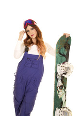 woman with red hair and snowboard stand hand by face