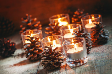 Christmas Christmas card with glowing small candle and fir cones
