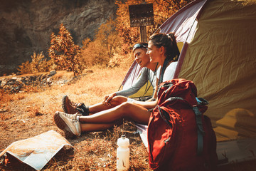 Photo sur Plexiglas Camping Couple camping. Young couple sitting in tent and relaxing.