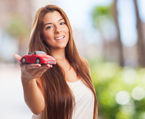 pretty young woman holding a red car toy