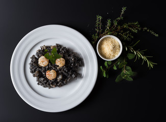 Black risotto with herbs and parmesan