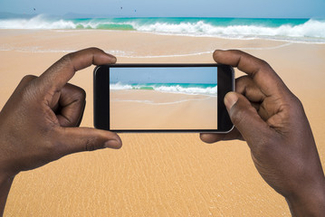 Man taking picture with mobile phone on a beach