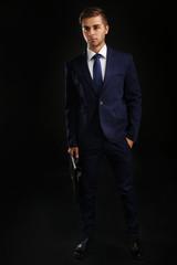 Elegant man in suit with briefcase on dark background