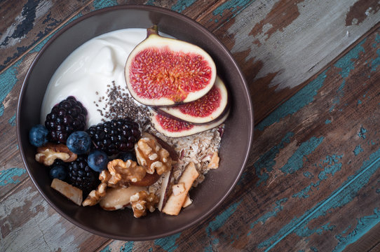 A bowl of healthy breakfast muesli with yogurt and topped with fresh fig, berries, walnuts, chia seeds and coconut shavings.