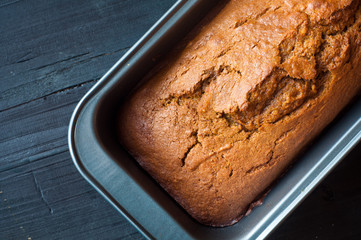 Freshly baked pumpkin bread cake in a baking tin. Perfect in Autumn Fall and served on a black wooden table.