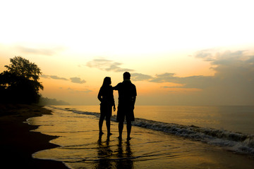 Stock Photo:.Silhouettes of romantic couple on tropical beach at