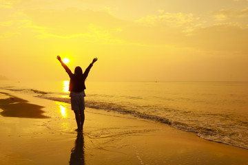 Stock Photo:. woman open arms under the sunset at sea