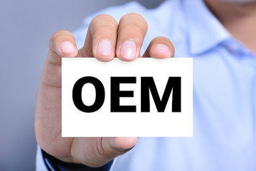 OEM letters (or Original Equipment Manufacturer) on the card held by a man
