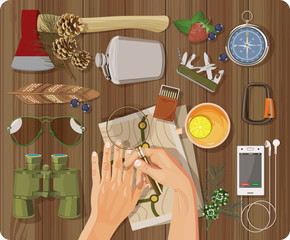 Workplace concept. Top view with textured table, feather, hands, phone, headphones, ax, flask, binoculars, matches, magnifying glass, map, sunglasses, carbine, cup of tea with lemon