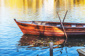 Wooden boat reflected in water of pond
