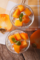 Chia seed pudding and persimmon close-up. vertical top view