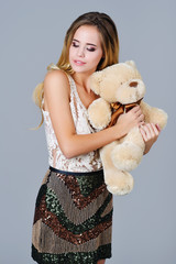 Beautiful fancy woman dressed in sequined skirt hugs bear toy