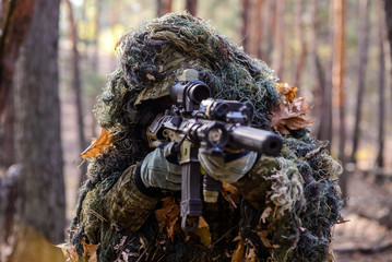 Sniper aiming from his rifle in forest/Portrait of sniper in the woods, which  aiming from his rifle
