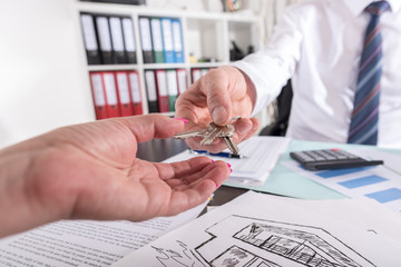 Estate agent giving keys to his customer
