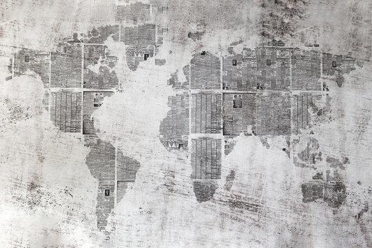 Muro grigio con  collage di fogli di giornali a forma del mondo